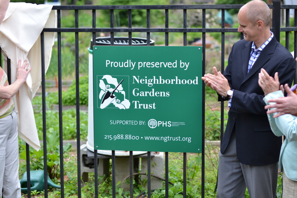 Drew Becker, President of the Philadelphia Horticultural Society (right) unveils the new logo for the Neighborhood Gardens Trust.